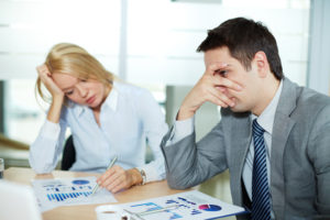 Sad business partners at workplace, focus is on confused male